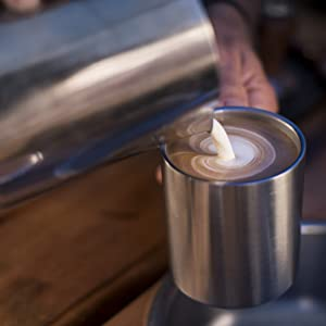 Man pouring milk into latte in stainless steel mug at coffee shop
