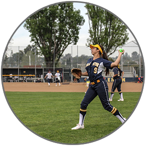 Softball player throwing a PowerNet weighted training balls for strength