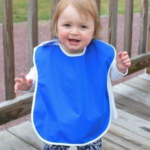 cute baby toddler girl smiling wearing large blue waterproof feeding bib
