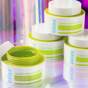 stacked jars of green tea wonder mask with one jar opened against a prismatic background