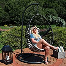 model shown sitting on egg chair on patio