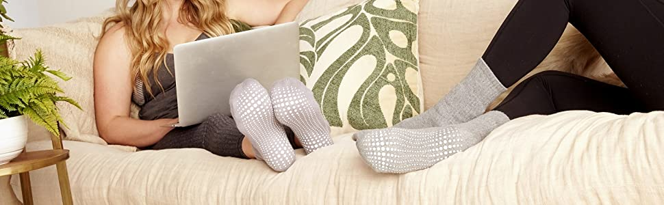 Woman on comfortable couch using laptop and with grey designer grip sock