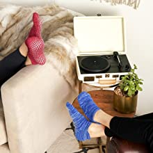 Pair of red and blue socks on feet resting on a couch