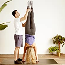 Man holding woman in headstand in yoga studio wearing grippy sticky socks