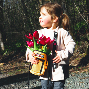 Little girl holding a Wild Wolf Outfitters water bottle sleeve with flowers in it