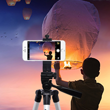 Boy in susnset releasing paper ballon with acuvar 50 inch tripod and rotating mount capturing moment
