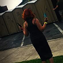 Lady using Tinkle Belle at dirty outhouse at brewfest
