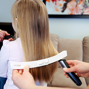 Mom cutting kids hair at home using Original CreaClip hair cutting tool