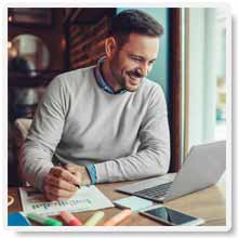 Man In A Good Mood Bright and Awake Focused On Working On His Laptop To Help Fuel His Busy Day