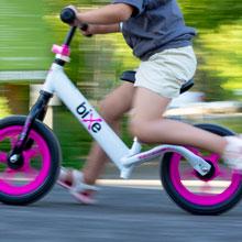 girl riding fast along path on her balance bike