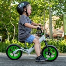 boy planting feet on ground to stay balanced on his bike