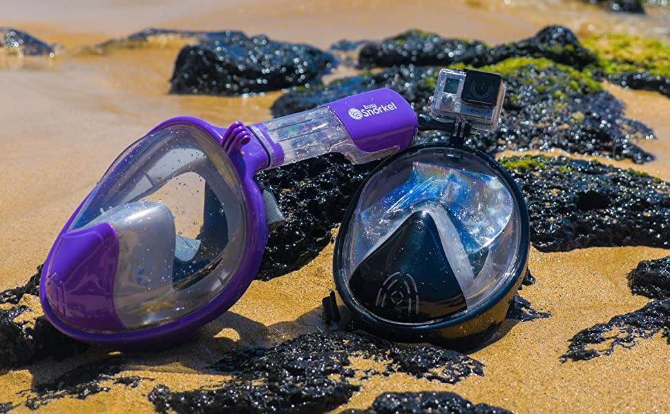 b2abecce37d6 Purple and Black full face snorkel masks on sand and rocks on a beautiful  beach in