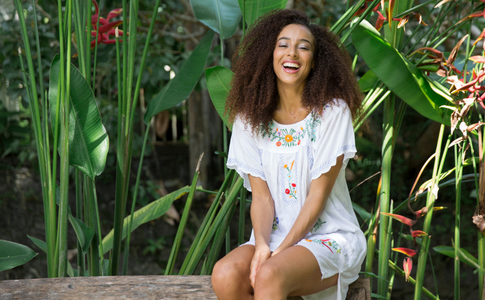 Woman sitting in tropical greenery wearing a white embroidered Mexican style short peasant dress