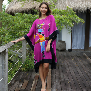 Woman standing on a deck wearing a tribal fuchsia Africa short beach dress swimsuit bikini cover up