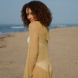 Woman on the beach wearing a tan long lightweight sheer cardigan open front hooded knit sweater