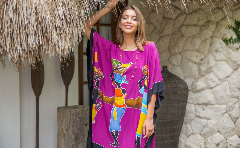 Woman standing near a hut wearing a tribal fuchsia Africa short beach dress swimsuit bikini cover up