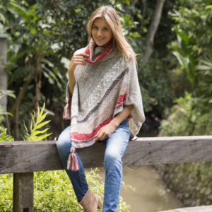 Woman sitting on a fence wearing a grey knit cowl neck soft pullover poncho sweater tasseled cape