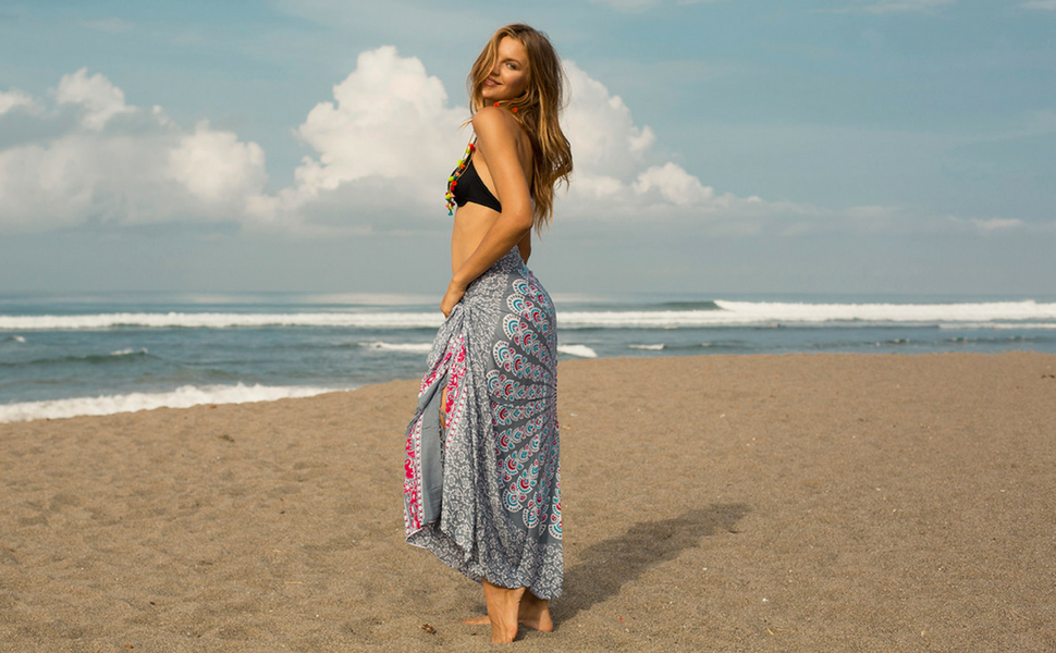 8cd9307795 woman on the beach wearing a grey womens sarong wrap bikini swimsuit cover  up with shell