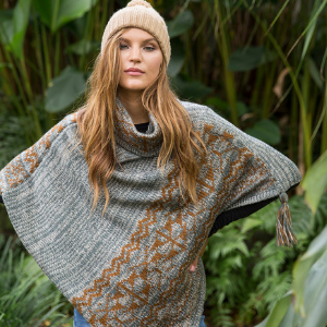 Woman standing in front of forest wearing a grey knit cowl neck soft pullover poncho sweater cape