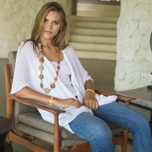 d2ff9b8f4e4 Woman sitting in a chair wearing a long white open front short sleeve  cardigan sweater shrug