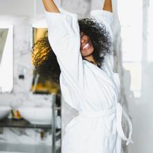 Woman in bath robe preparing argan bath oil soak