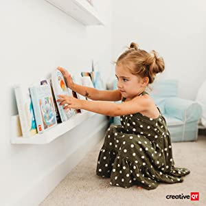 Little girl begins helping around the house by tidying and organizing the bookshelf in her bedroom