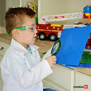 Image of a young boy looking at the PAS product with magnifying glass