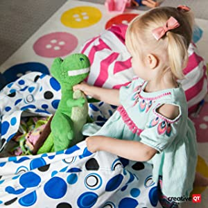 Little girl stuffing her Stuff N Sit with her collection of stuffed animals