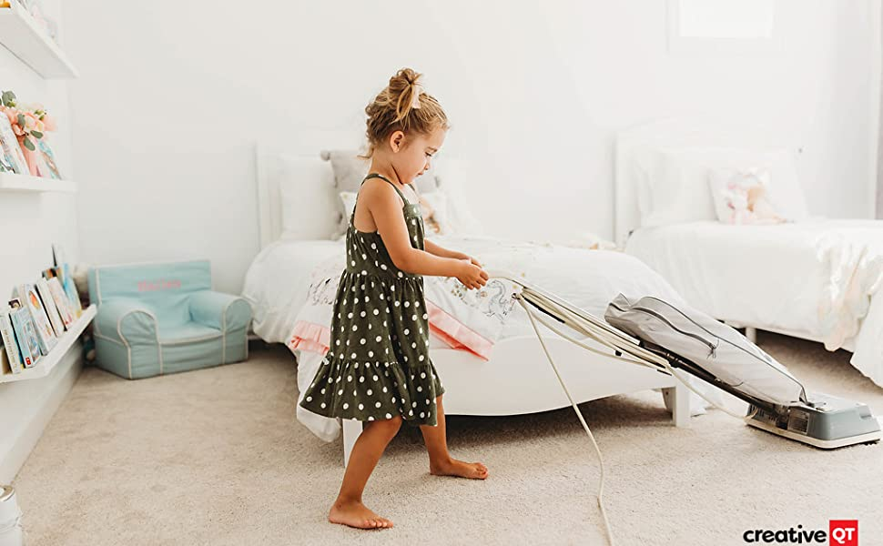 Little girl continues to help clean her bedroom by carefully vacuuming the carpet around the beds