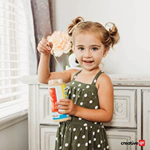 Little girl is excited to open her can of chore sticks to see what surprise stick she will draw