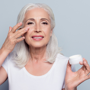 Image of older woman using ointment, pleased