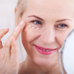 image of older lady applying cream under eye
