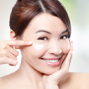 image of lady applying cream under eye smiling