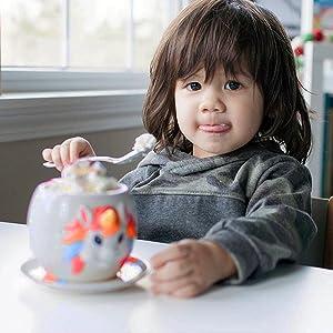 A child enjoys some unicorn stuff for girls with her unicorn rainbow mug