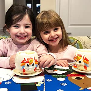 Two girls with their unicorn gifts, drinking from their unicorn cups