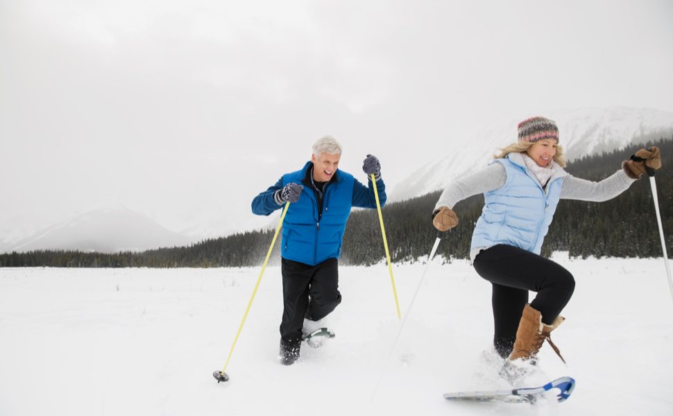 Senior couple smiling while cross country skiing