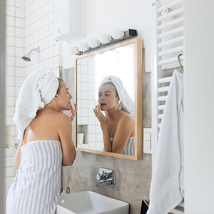 Woman in towel applying moisturizer as a part of daily skin care routine.