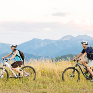 Family biking on a trail with mountains in the background