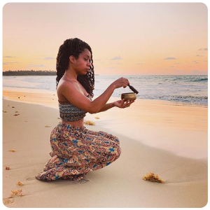 beautiful woman kneeling by the sea shore using a striker on her singing bowl