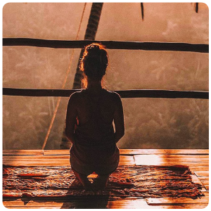 a woman kneeling on a yoga mat with her arms rested on her lap