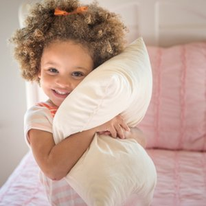 little girl hugging toddler pillow