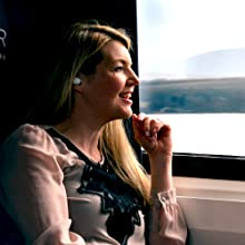 Adult woman on train wearing in-ear bluetooth headphones while smiling