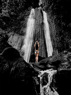 woman wearing a bikini in front of a waterfall