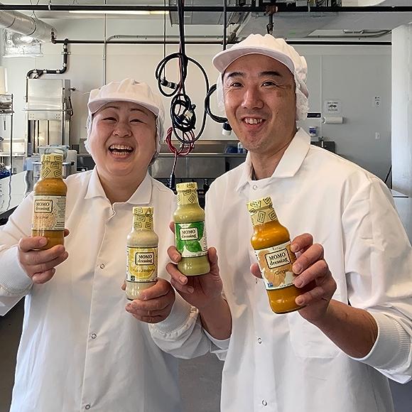 MOMO Dressing Founders Masaki and Yukimi Momose holding product