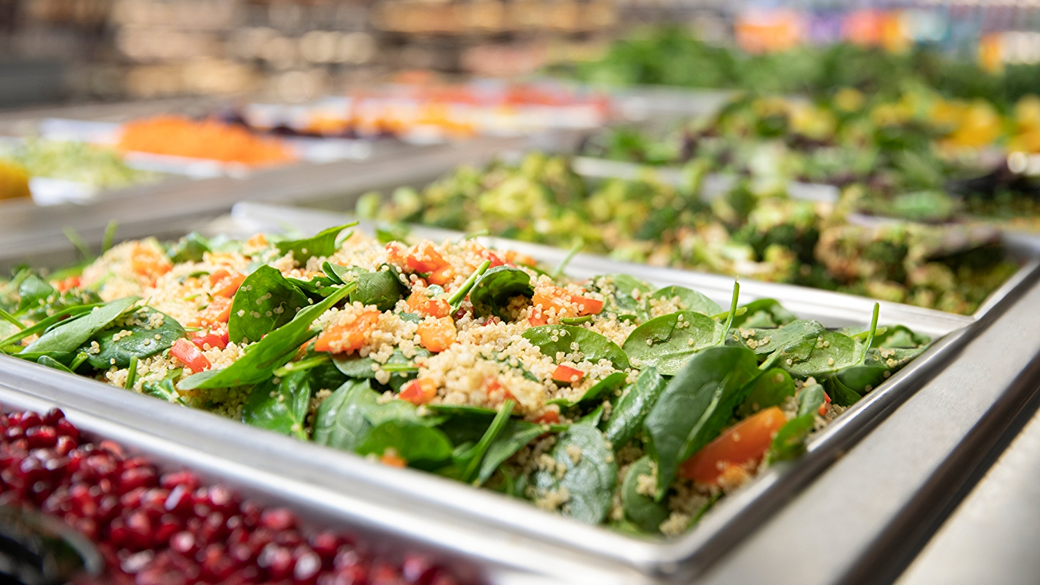 salad bar with spinach and couscous in focus