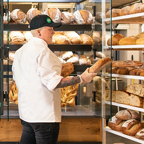 man from whole foods bakery department holding bread