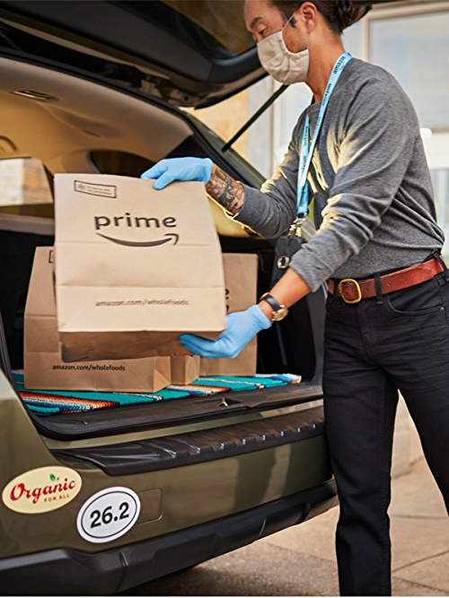 Shopper putting pickup order in a car trunk