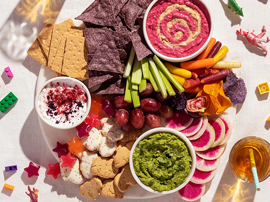 overhead shot of colorful kid's snack board with dips, chips and more