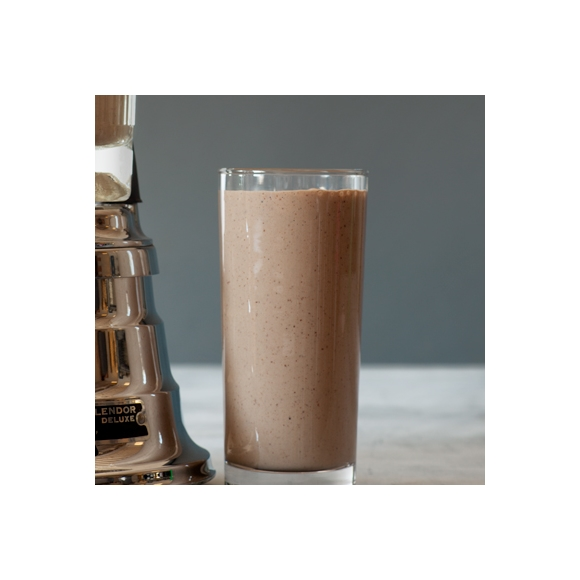 Chocolate smoothie in a glass next to blender.
