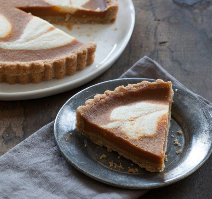 A slice of Kite Hill's vegan Pumpkin Cheesecake Tart on a plate.
